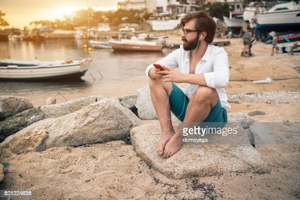 Handsome hipster listening music and looking at the sea