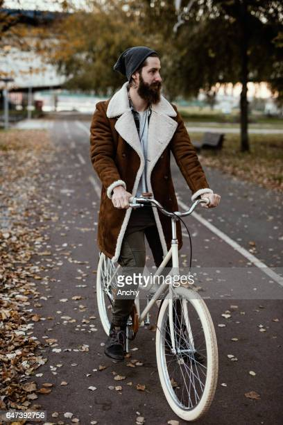 Handsome hipster on a vintage bicycle in the park
