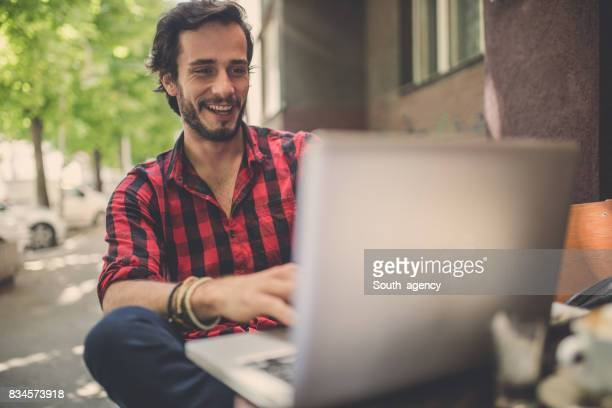 Handsome hipster using laptop