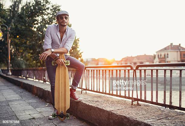 Handsome hipster with longboard