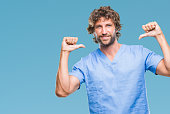Handsome hispanic surgeon doctor man over isolated background looking confident with smile on face, pointing oneself with fingers proud and happy.