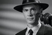 Greyscale portrait of a serious handsome intelligent young detective in a stylish vintage style hat holding a magnifying glass to his eye as he stares at the camera