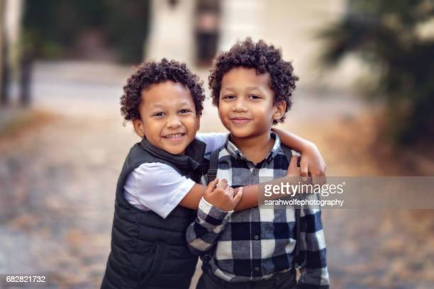 handsome l twin brothers hugging and standing in an urban scene