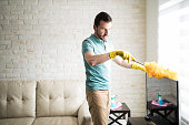 Single man dusting his furniture to keep the dust away from them and have a clean house