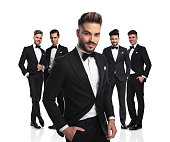 handsome leader of young men in black tuxedoes standing on white background, looking relaxed