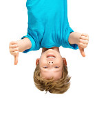 Funny photo of handsome little boy hanging upside down on white background. Boy smiling and showing thumbs up