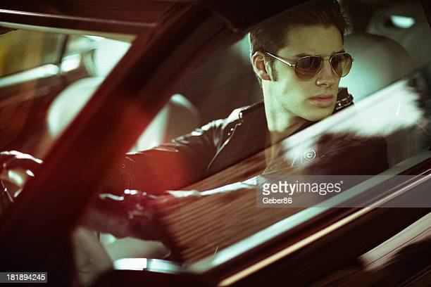 Handsome male model posing in car