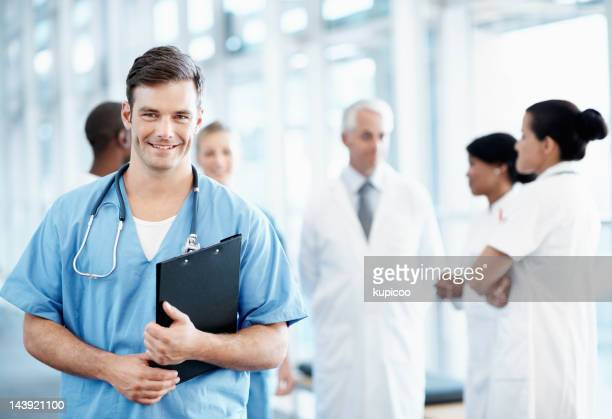 Handsome male nurse with medical team in background