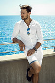 Handsome man in whit clothes resting by the sea