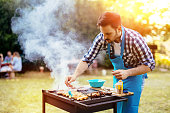 Handsome male preparing barbecue outdoors for friends