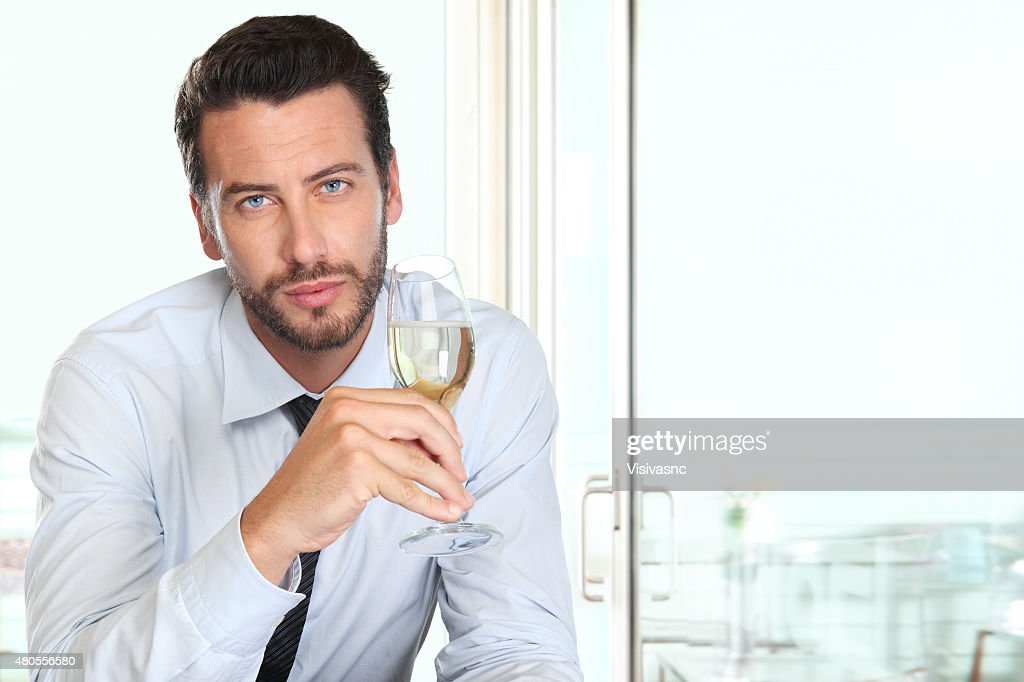 handsome man drinking a glass of sparkling wine white : Stock Photo
