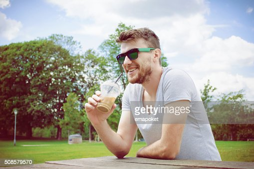 Handsome man drinking coffee in park : Stockfoto