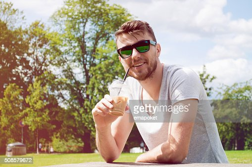 Handsome man drinking coffee in park : Stock Photo