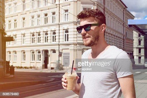Handsome man drinking coffee on street : Stock Photo