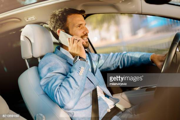 Handsome man driving a car and using smartphone