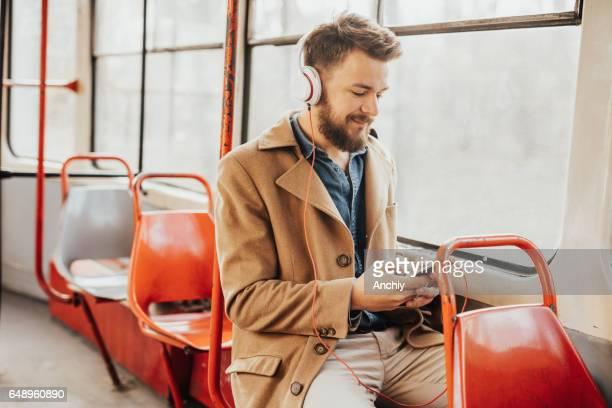 Gut aussehender Mann seine Arbeit mit der Straßenbahn unterwegs Musik genießen