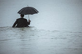 Rear view on a handsome man wearing full suit and holding umbrella, walking through the water on a rainy day. The man waded halfway in the water. Selective focus, waist up, copy space has been left.