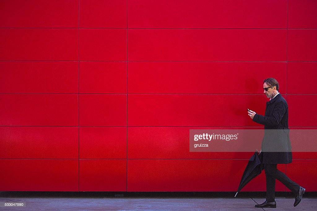Handsome man in black walking beside the red wall : Stock Photo