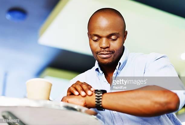 Gut aussehender Mann im Café Schecks seine Uhr