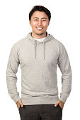 An attractive man in his 20s standing against a white background wearing a grey hood shirt smiling, looking at camera.