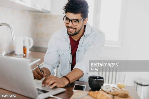 Handsome man in the kitchen using laptop