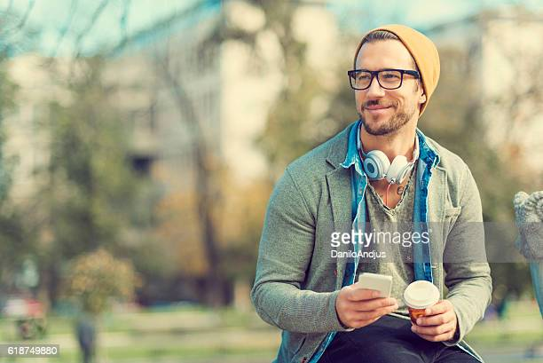 handsome man in the park using his smartphone