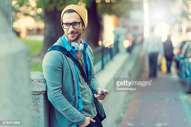 handsome man in the street holding his smartphone
