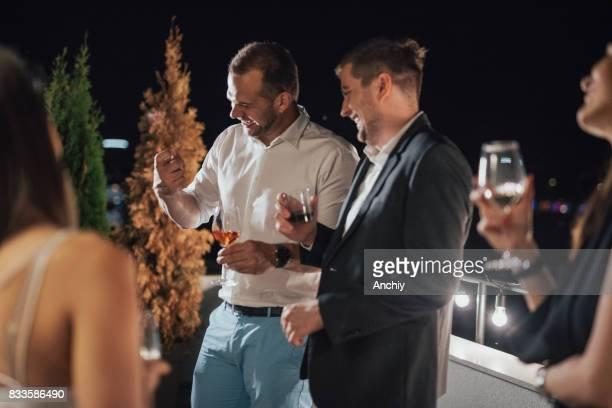 Bel homme en chemise blanche est raconter une blague à ses amis.