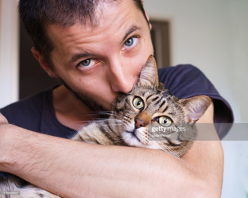 Handsome man kissing and holding a cat