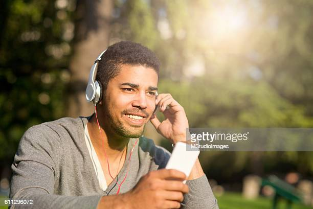 Handsome man listening to music in the park.