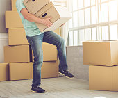 Cropped image of handsome mature bearded man in casual clothes carrying boxes while moving to the new apartment