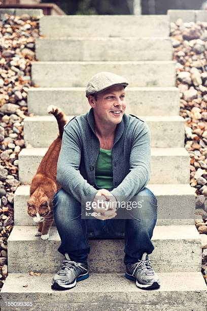 Handsome man outdoors with cat