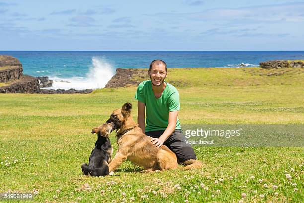Handsome man playing with dogs at Easter Island