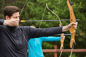 Handsome man practicing archery at the archery range