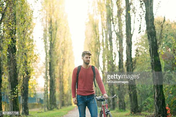 Handsome man pushing his bicycle at the park.