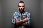 Handsome man reading and praying over Bible in a dark room over gray texture