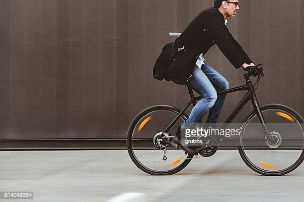 Handsome man riding bicycle beside the grey wall