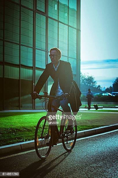 Handsome man riding bicycle beside the modern office building