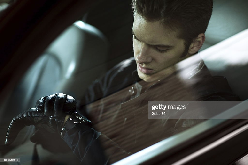 Handsome man siting in car and looking at his watch