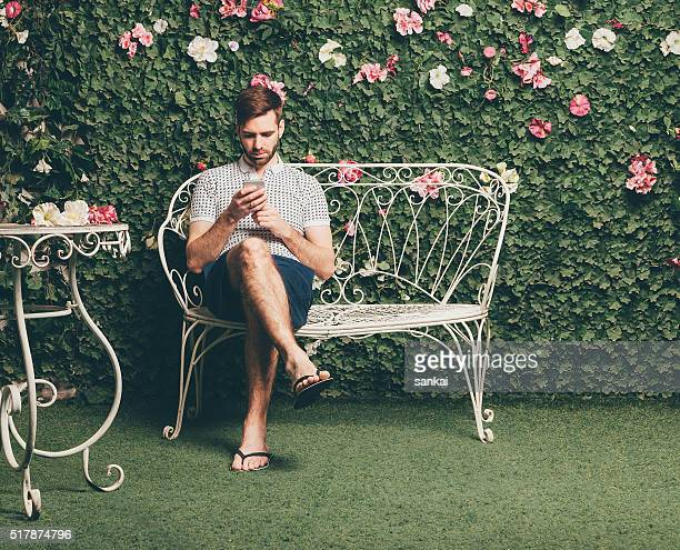Handsome man sits on a bench and typing text message