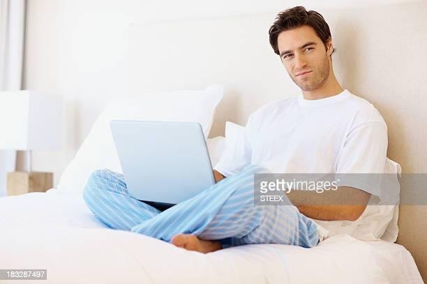 Hombre atractivo sentado en la cama con la computadora portátil