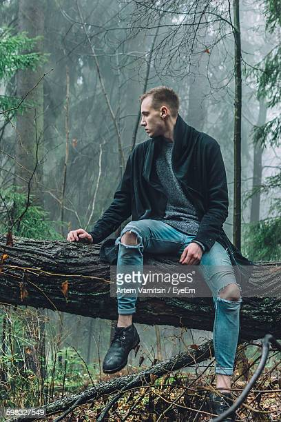 Handsome Man Sitting On Fallen Tree In Forest