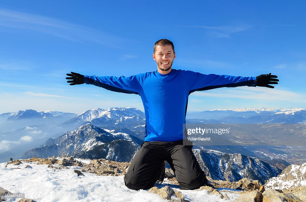 Handsome man sitting on top of mountain in winter
