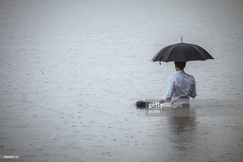 Handsome man standing in water and holding umbrella during rain : Stock Photo