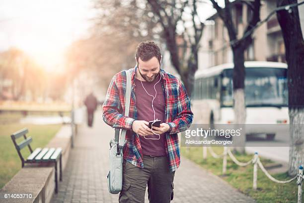 Handsome Man Talking on Smartphone and Walking on City Street