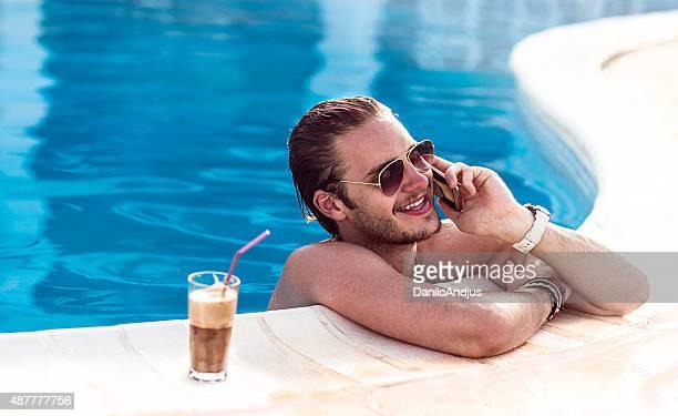 Bel homme parler au téléphone dans la piscine