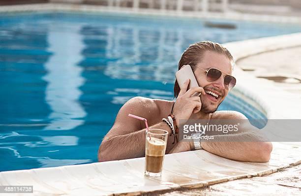Bel homme parler au téléphone en profitant de la piscine