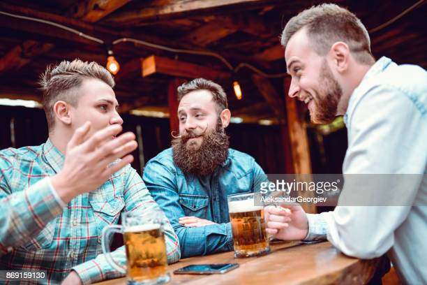 Handsome Man Telling Funny Story to his Best Friends While Drinking Beer in a Pub