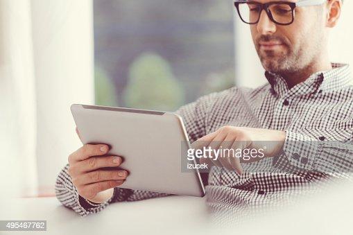 ハンサムな男性のデジタルタブレットを使用して、
