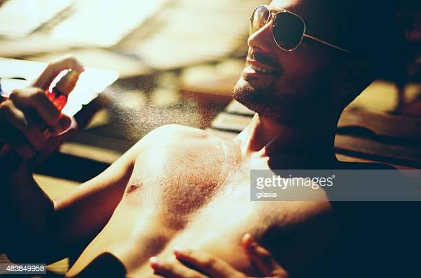 Gut aussehender Mann mit Sonnencreme mit.